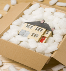 miniature house packed in a cardboard moving box
